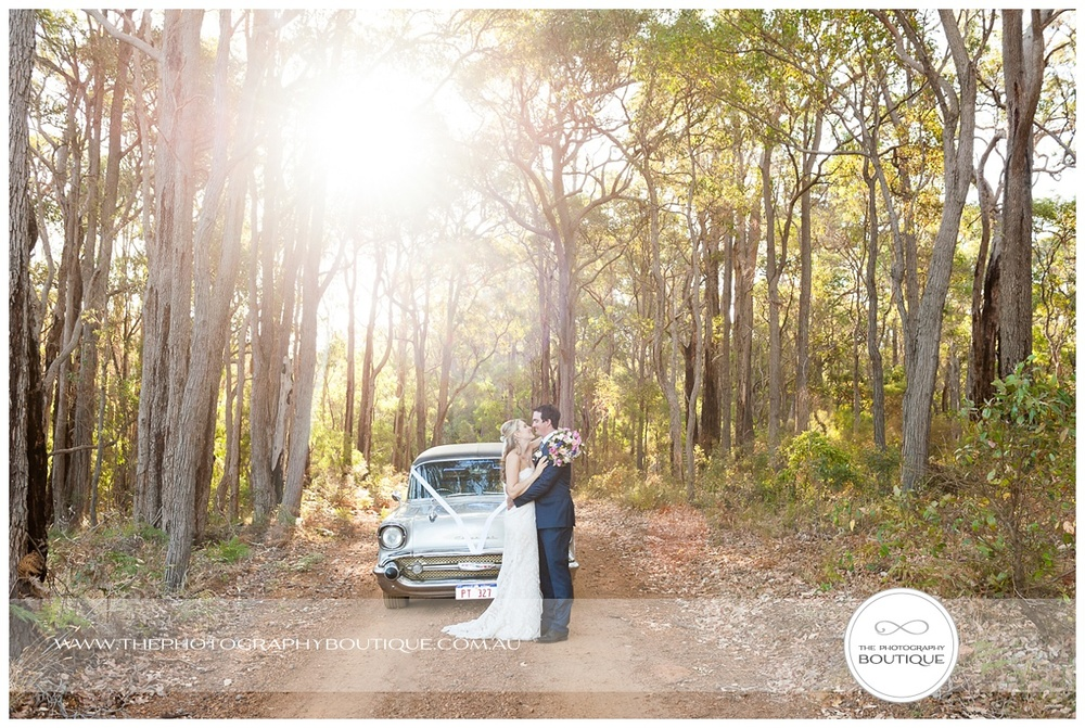 bride and groom with chevy limo in sun drenched trees margaret river