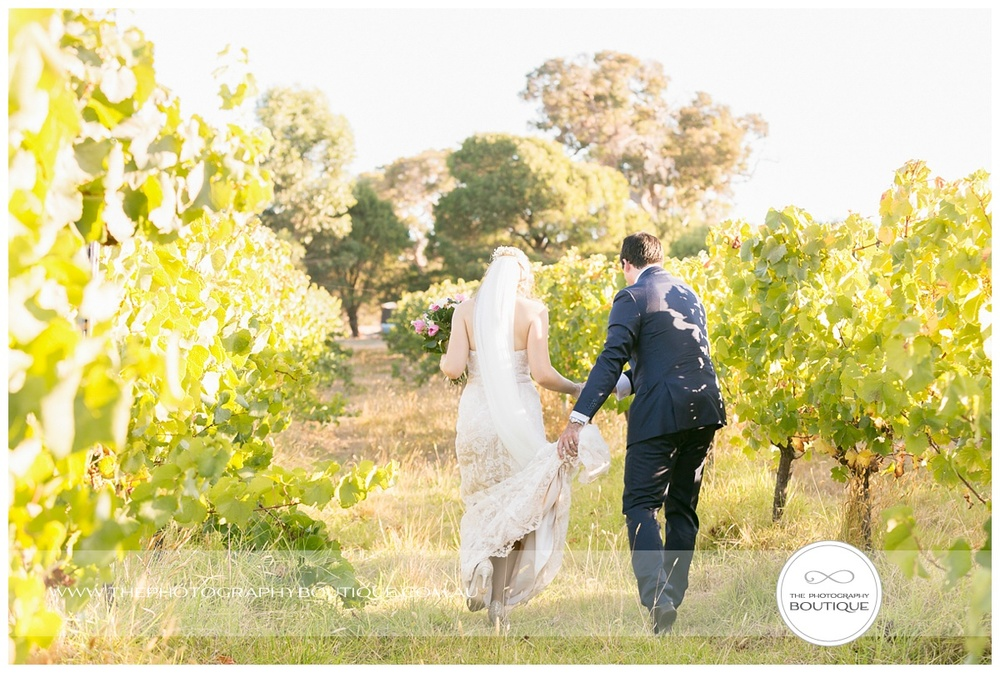 bride and groom walking through the vines at margaret river winery