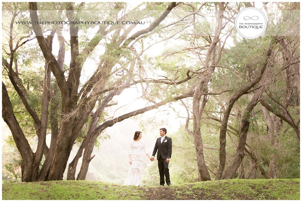 Bride and groom holding hands under the trees at Caves House Yallingup
