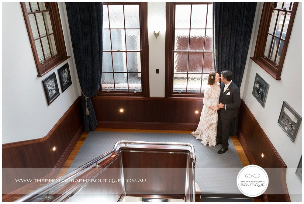 Bride and groom on the art deco staircase at Caves House Yallingup