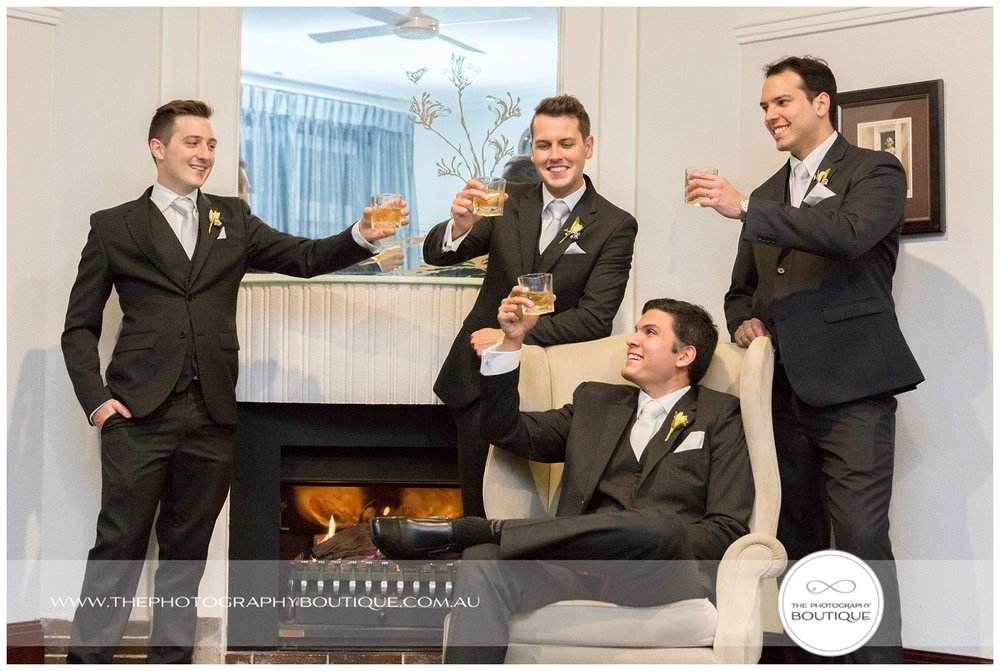 Groomsmen toasting with whiskey in front of the fire at Caves House Yallingup
