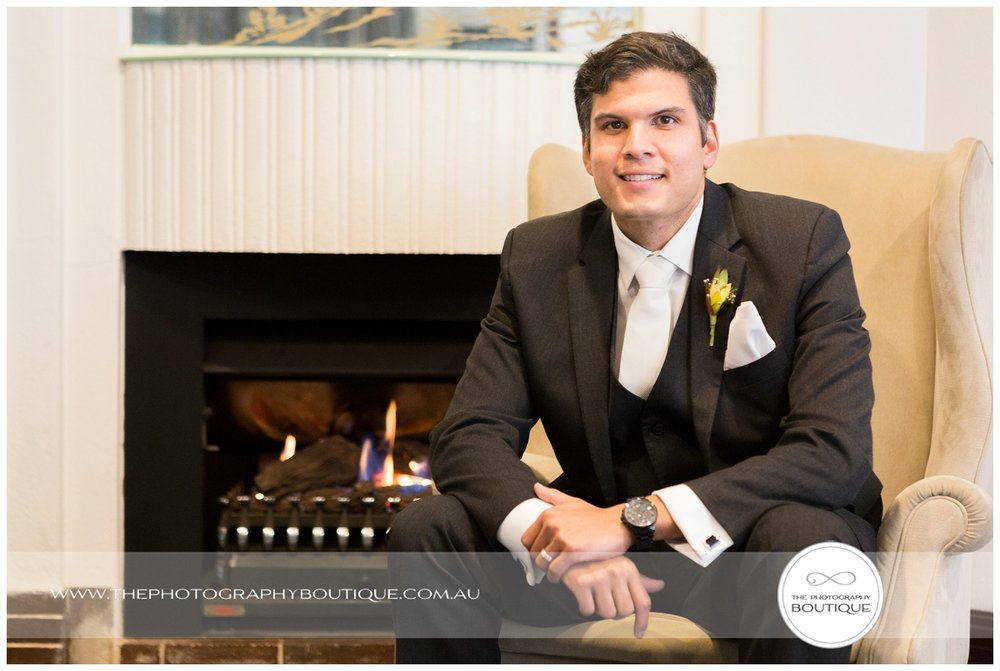 portrait of groom in front of the fireplace at Caves House Yallingup