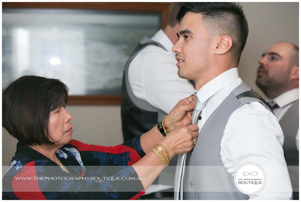 mum helping groom with his tie