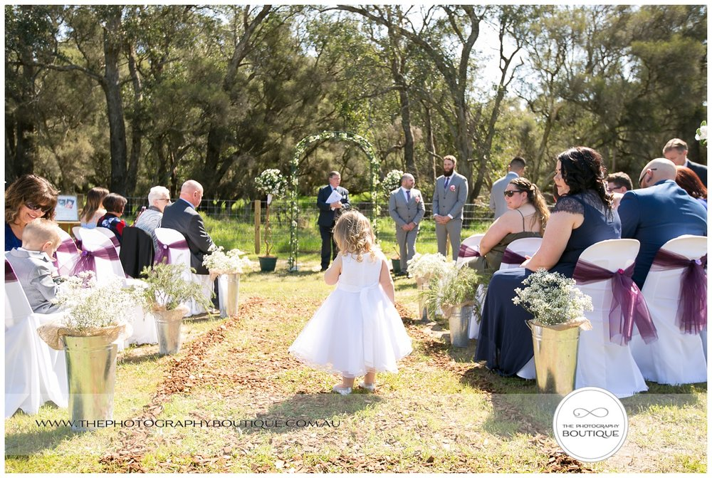 flower girl walking down the aisle at roelands backyard wedding