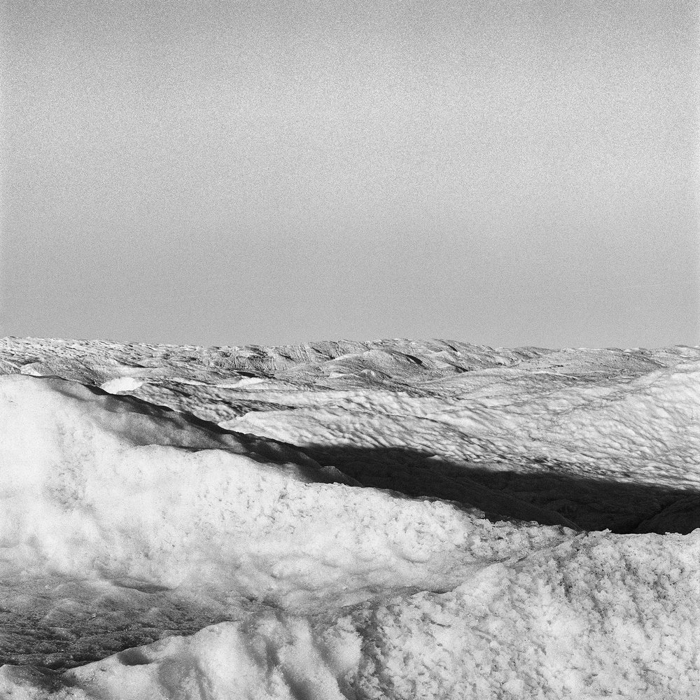 SERMERSUAQ  A photographic study of Sermersuaq, Greenland's ice sheet.  Greenland, 2014   Greenland's deteriorating ice sheet is one of the world's last empty places and truly sublime landscapes. On an expedition to the Arctic Thomas's work focuses on the immense retreat and melting of the ice sheet's Western edge where a new black, rocky desertscape is expanding as the ice creaks, groans and disintegrates. Thomas's resulting abstract photographic explorations reveal the dynamic, sublime and enigmatic qualities of Sermersuaq, inviting the viewer to contemplate their own relationship with this isolated, fragile and ephemeral icescape.