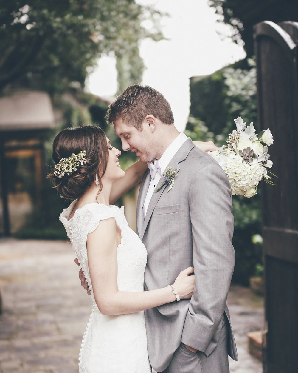 Bride and Groom Embrace in WW Courtyard in front of gate.jpg