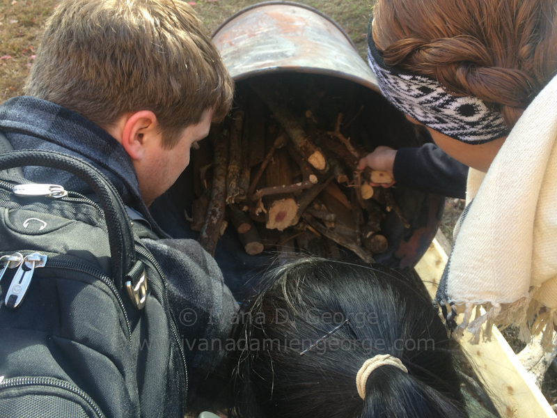 Students load the inner barrel with wood that will become biocha