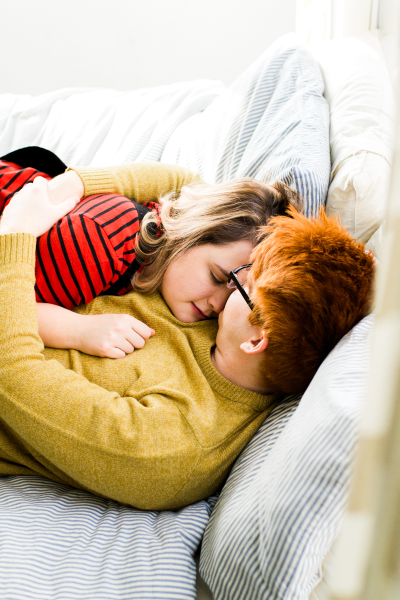 cuddling together on a bed during an intimate in-home couples session in Kansas City, MO