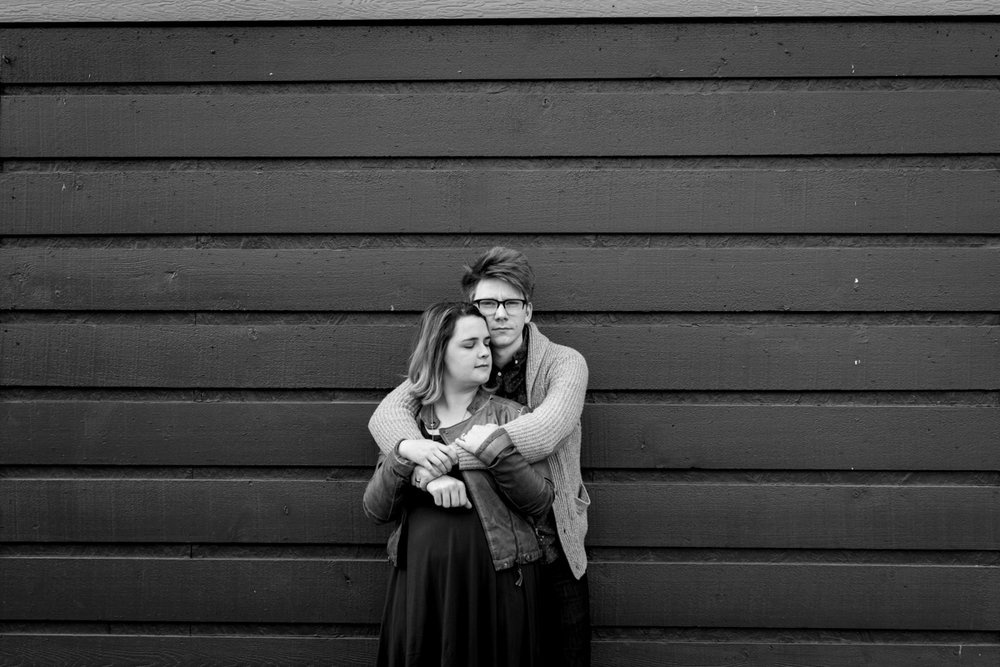 urban engaged or married couple leaning against gray wall engagment photography couples photography Westport Kansas City, MO