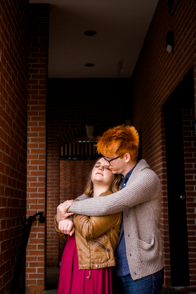 urban engaged or married couple cuddling under brick doorway photography couples photography Westport Kansas City, MO