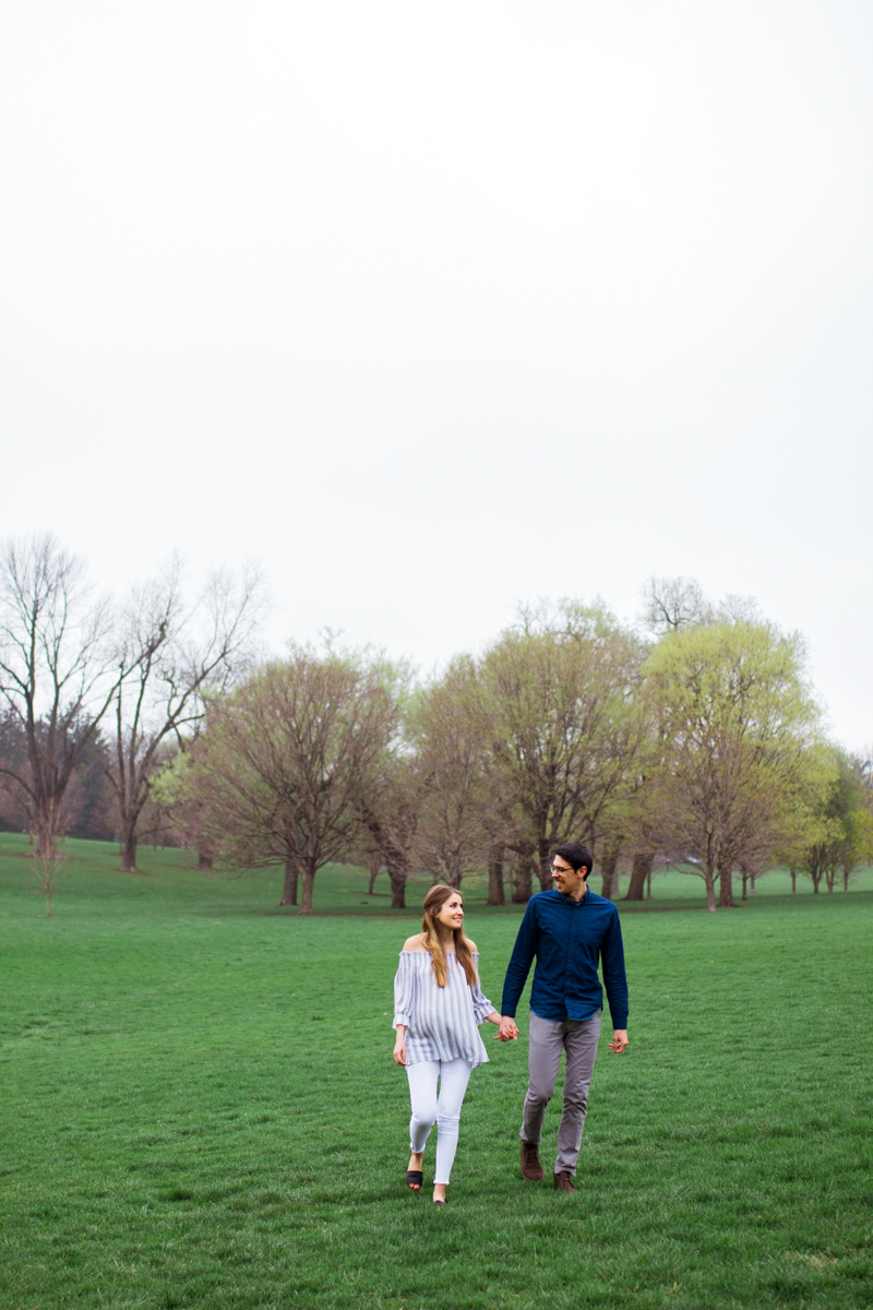 Kansas City Loose Park spring maternity session walking across the hills holding hands Kansas City Maternity photographer