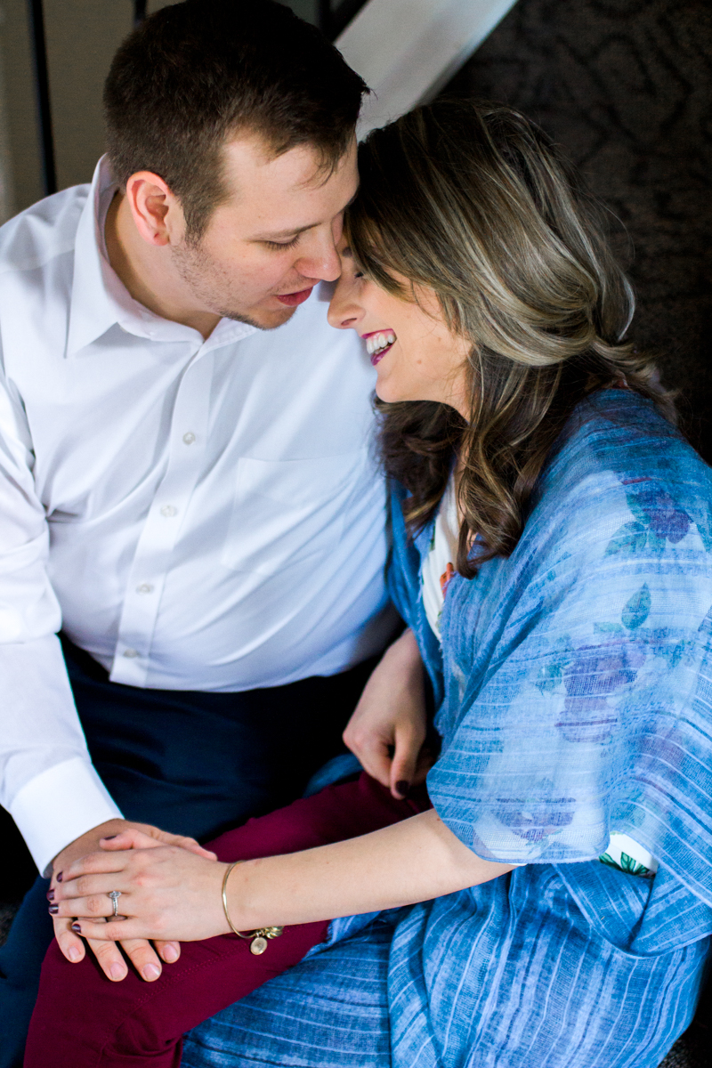 Kansas City lifestyle photographer in home couples session cuddling and laughing on the stairs engagement photos