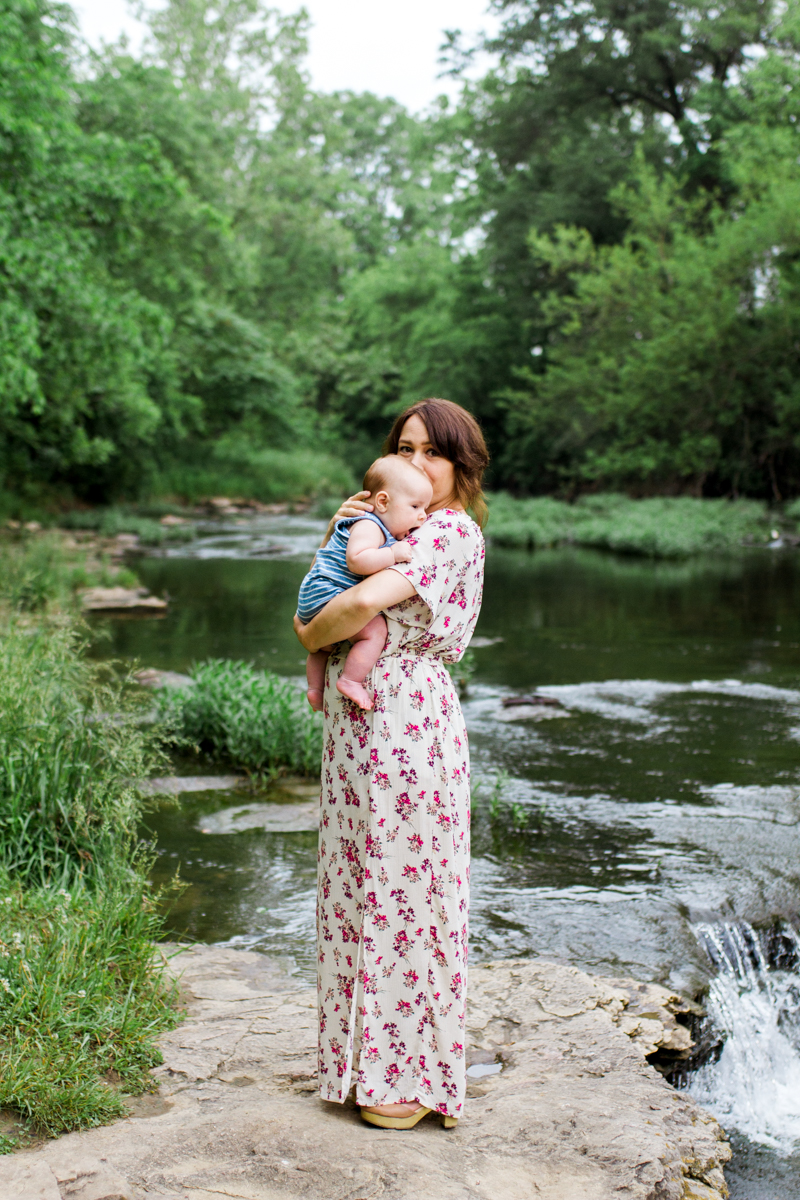Rebecca Clair Photography Kansas City MO lifestyle family photographer Line Creek Trail Family Session mother holding baby by a waterfall