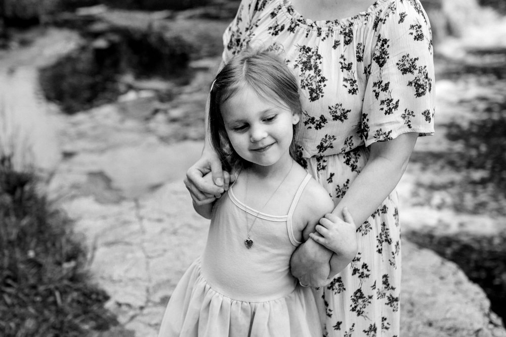 Rebecca Clair Photography Kansas City MO lifestyle family photographer Line Creek Trail Family Session mother and daughter cuddling together black and white photo
