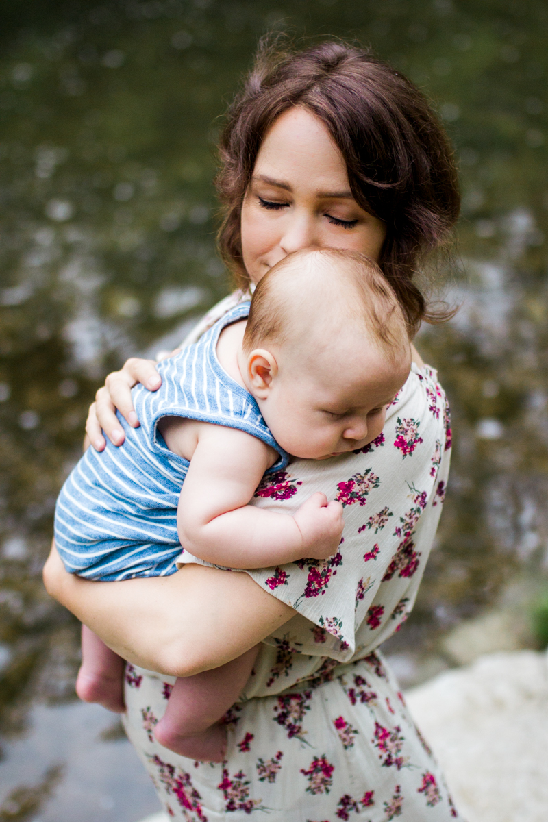 Rebecca Clair Photography Kansas City MO lifestyle family photographer Line Creek Trail Family Session close up of mother holding baby by the creek