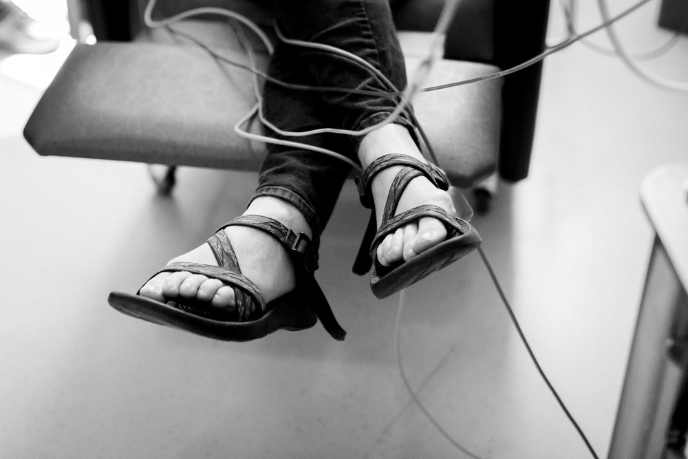 Rebecca Clair Photography lifestyle NICU newborn photography Children's Mercy Hospital mother's feet with cords black and white photo