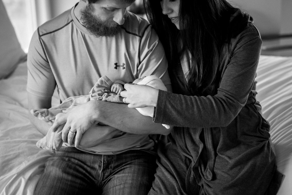 Kansas City lifestyle newborn photographer, Kansas City newborn photographer, Kansas City newborn photos, Kansas City in-hom newborn session, parents cuddling baby on bed, black and white photo