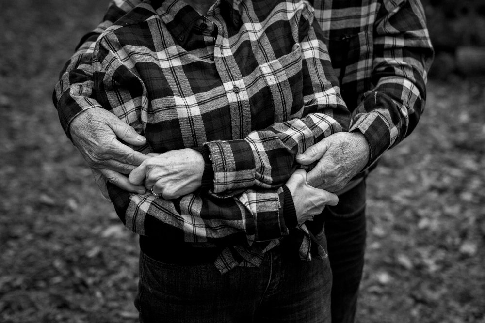 Kansas City lifestyle photographer, Kansas City family photographer, extended family session, fall family photos in the woods, older couple embrace, grandparents portrait, black and white portrait