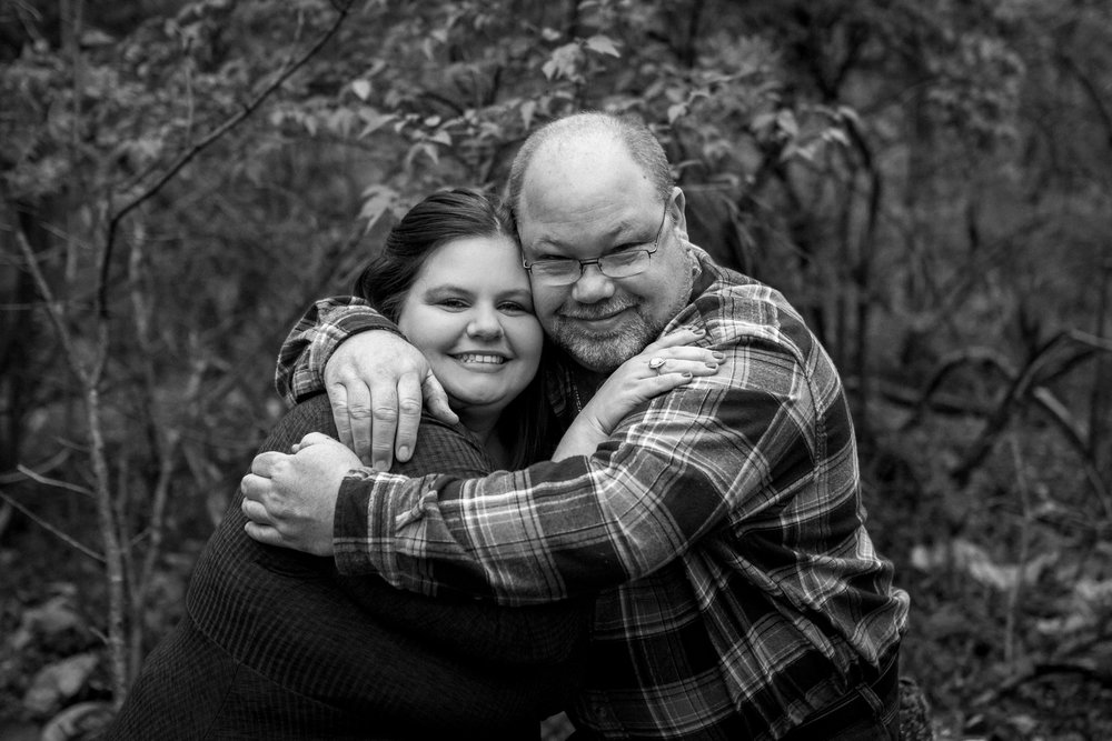 Kansas City lifestyle photographer, Kansas City family photographer, extended family session, fall family photos in the woods, father and grown daughter hugging, black and white photo