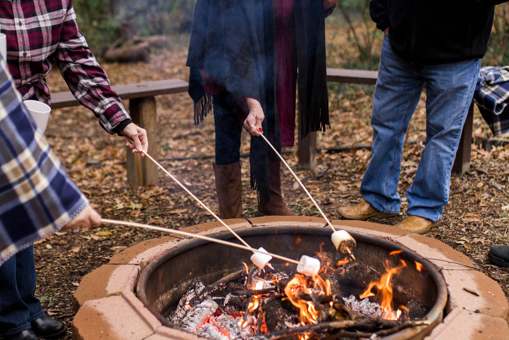 Kansas City lifestyle photographer, Kansas City family photographer, extended family session, fall family photos around a fire, roating marshmallows over the fire