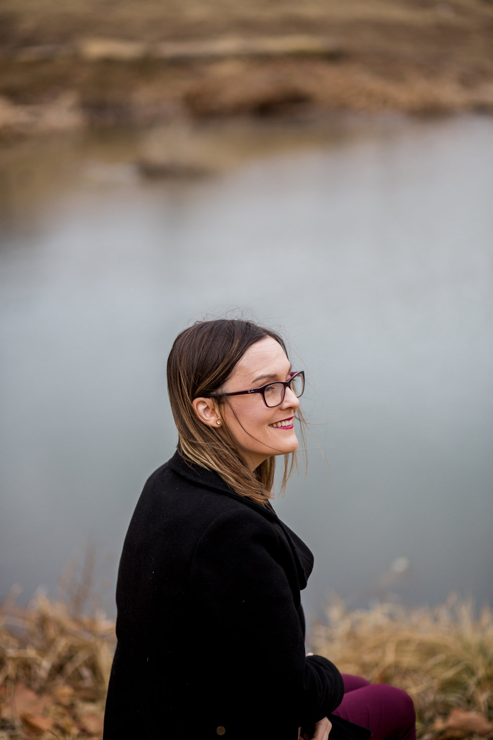 Candid portrait of woman sitting by winter pond, Kansas City lifestyle photographer, Kansas City senior photographer, Kansas City small business headshots, Kansas City lifestyle blogger, candid portrait, winter portrait session, Penn Valley Park