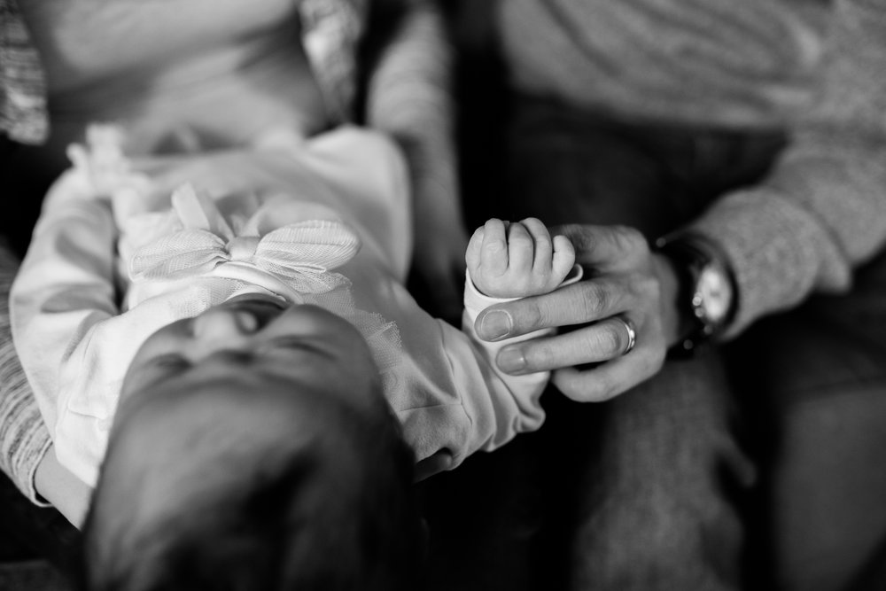 father holding his newborn daughter's hand, black and white close up of hands, Kansas City lifestyle newborn photographer, in-home newborn session