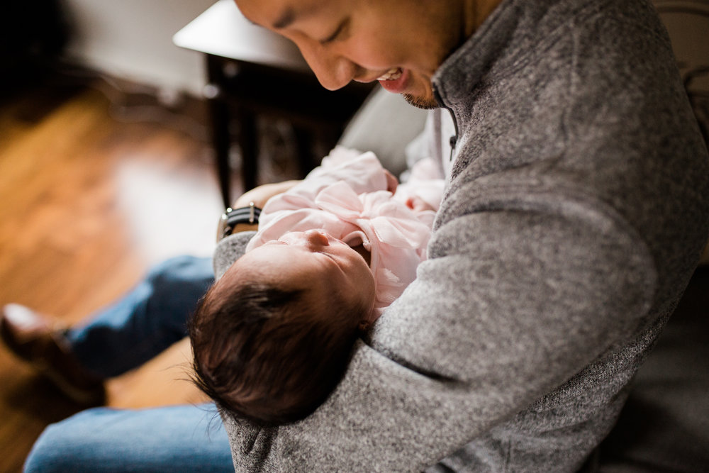 portrait of father cuddling his newborn daughter, Kansas City lifestyle newborn photographer, in-home newborn session