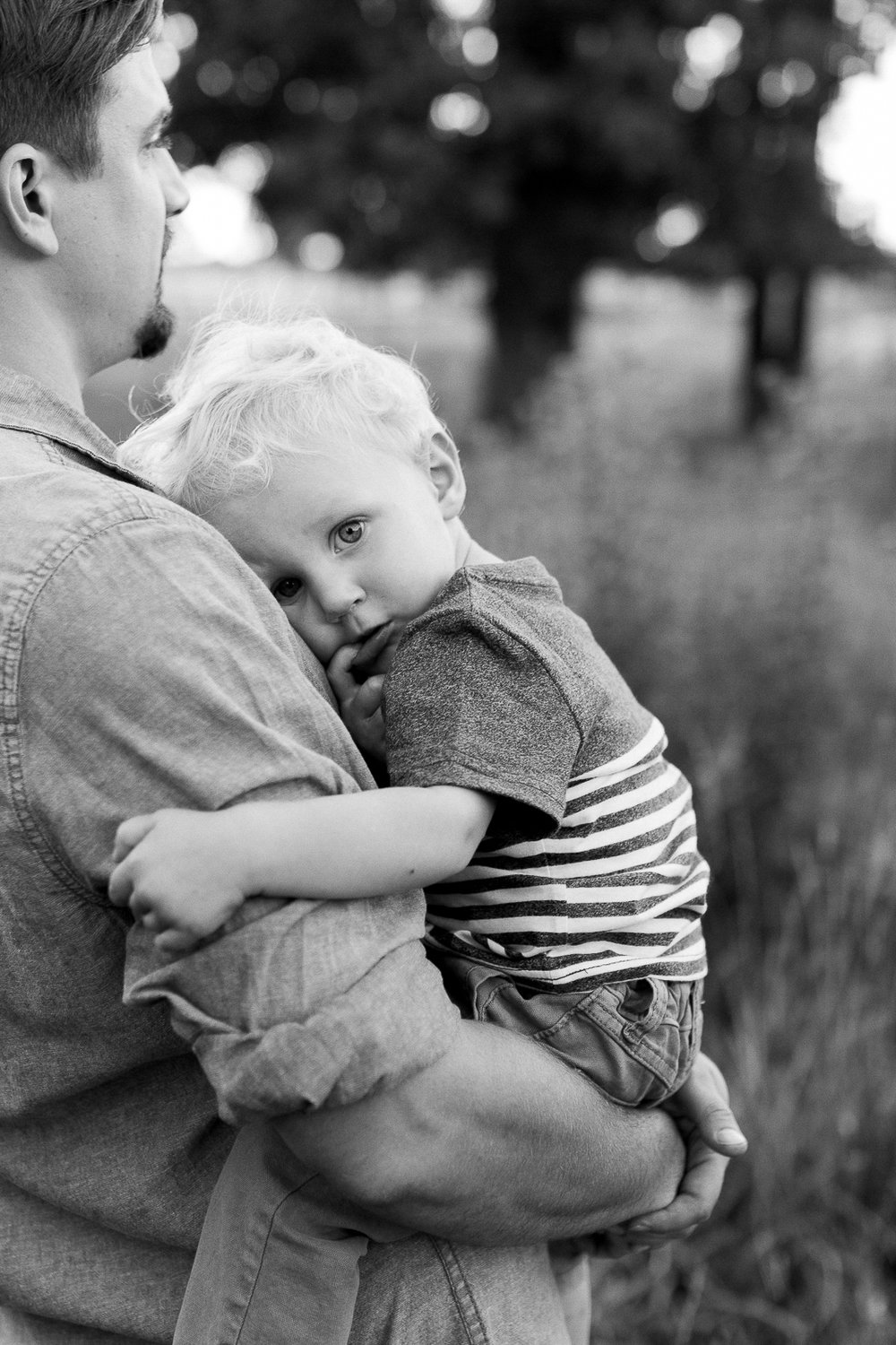 Black and white candid portrait of father holding son in evening light, Kansas City family lifestyle photo session