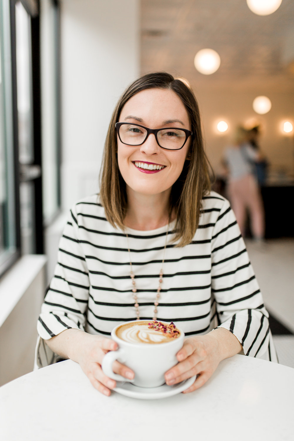 Smiling woman drinking a latte in a coffee shop, Kansas City lifestyle photographer, Kansas City senior photographer, Kansas City small business headshots, Kansas City lifestyle blogger, candid portrait, winter portrait session, Monarch Coffee