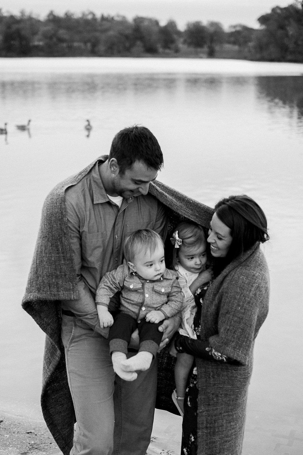 Candid black and white photo of family wrapped in a blanket, Kansas City family photographer, sunrise family session at Shawnee Mission Park, Rebecca Clair Photography