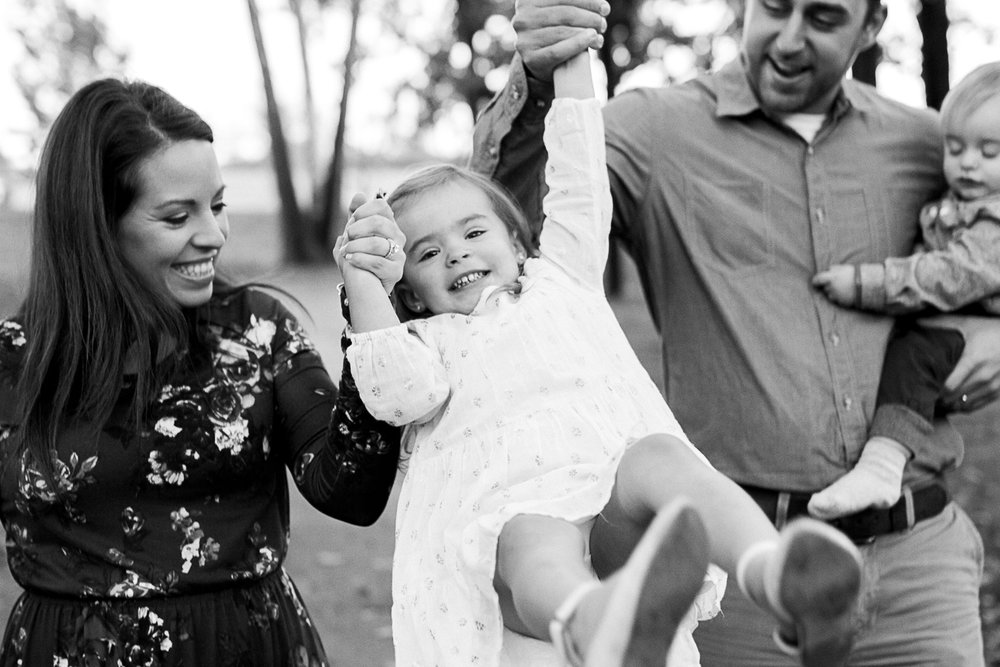 Black and white candid photo of family swinging daughter at the park, Kansas City lifestyle photographer, Shawnee Mission Park, Rebecca Clair Photography