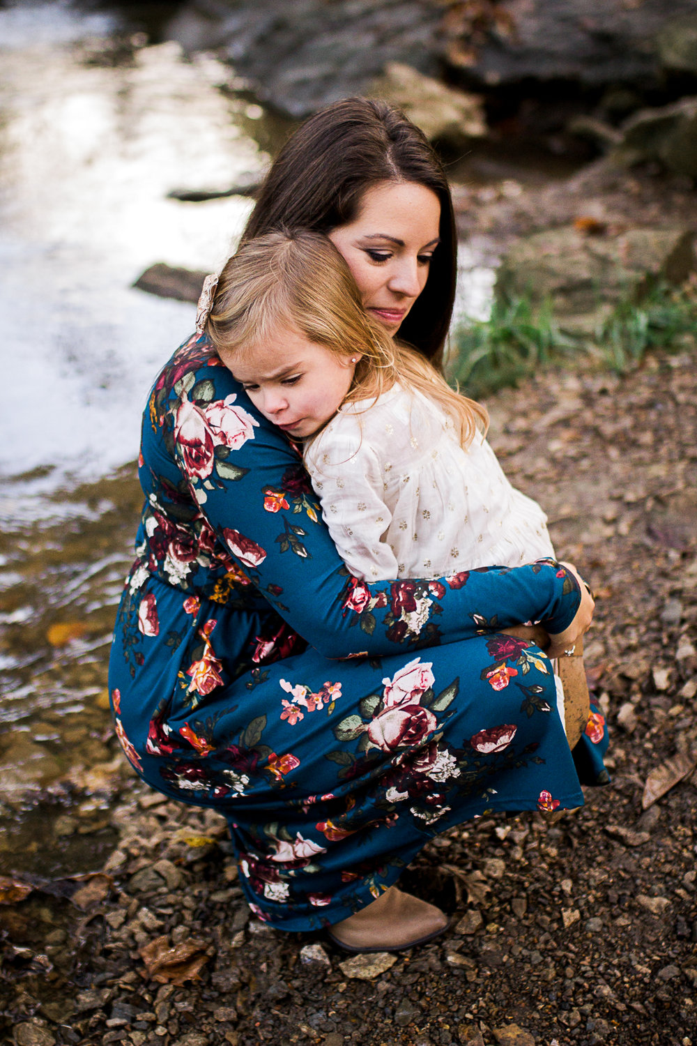 Mother embraces daughter by the stream, candid family photography, Shawnee Mission park sunrise session, Rebecca Clair Photography