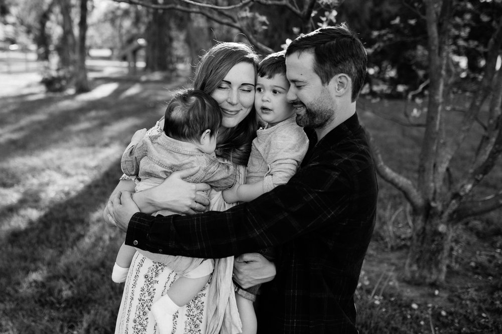 Black and white photo of family hugging, emotional family photos, Kansas City family photographer, Rebecca Clair photography