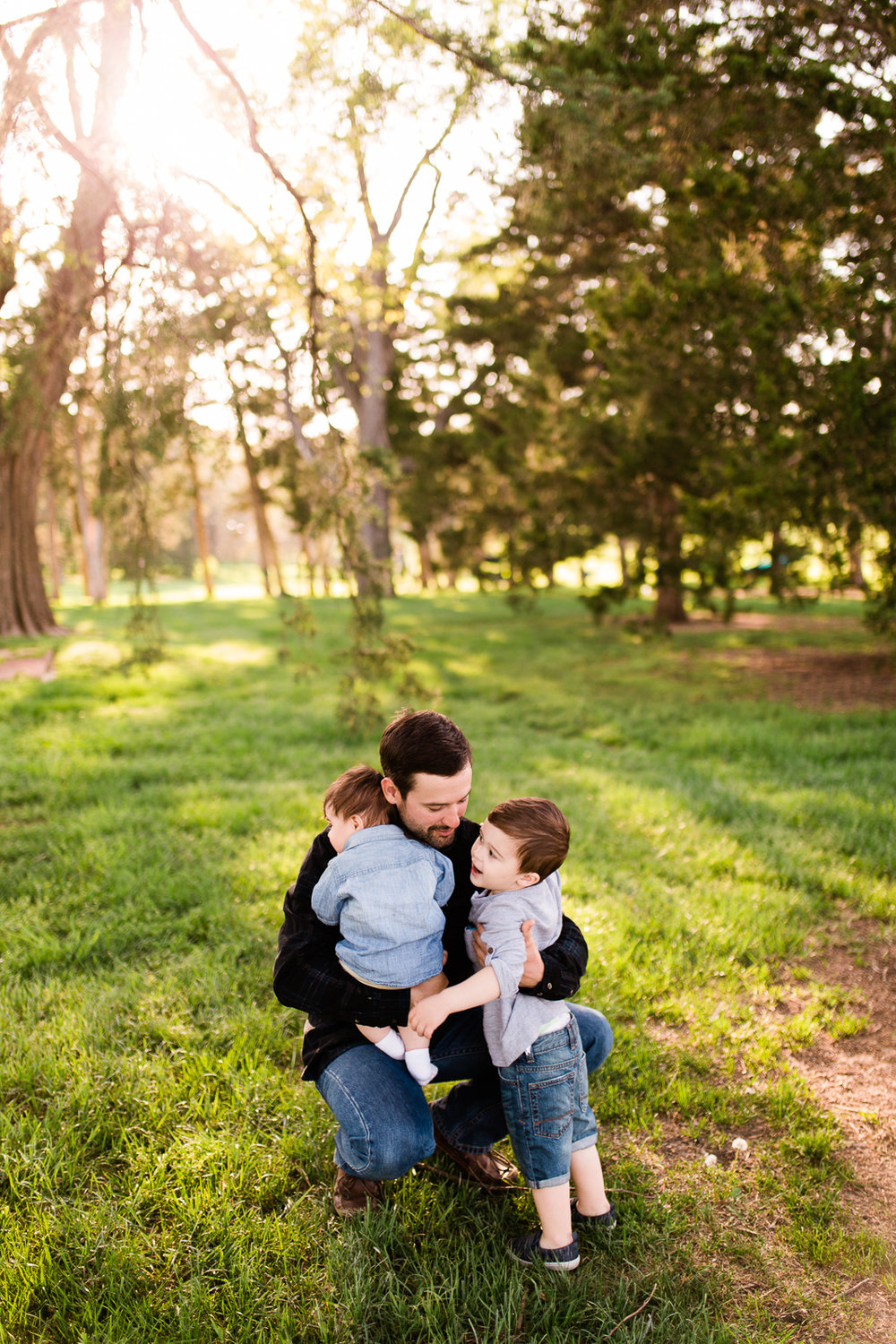 Father cuddles his sons in the evening light, Loose Park family session at golden hour, Kansas City family photographer, Rebecca Clair Photographer