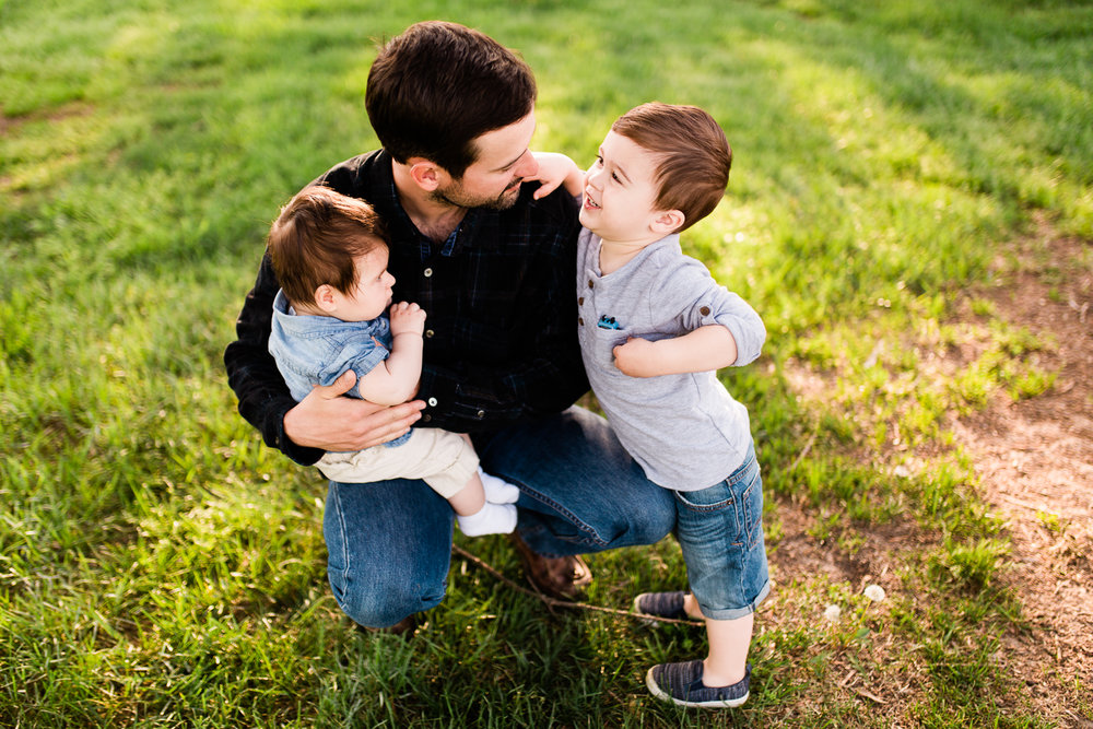 Father cuddles his sons in the evening light, Loose Park family session at golden hour, Kansas City lifestyle photographer, Rebecca Clair Photographer