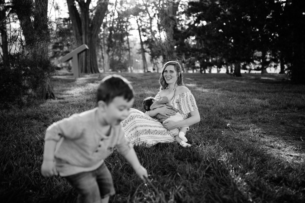 Black and white portrait of mother breastfeeding her baby while her toddler plays nearby, Kansas City breastfeeding session, lifestyle family photographer, Rebecca Clair Photography