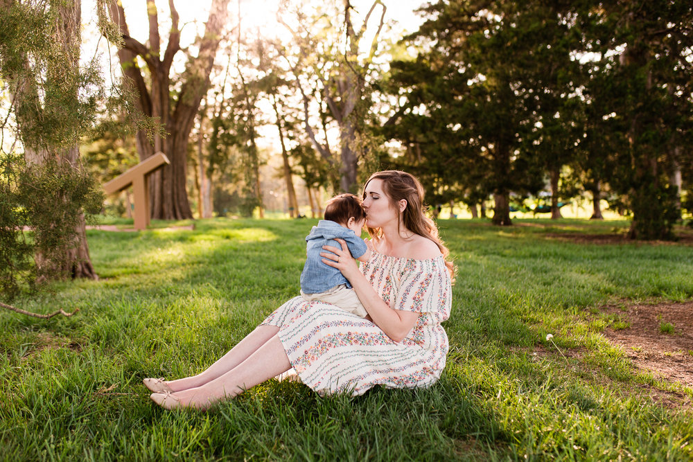 Mother kisses her son in a grove of trees, Loose park golden hour session, Kansas City family photographer, Rebecca Clair Photography