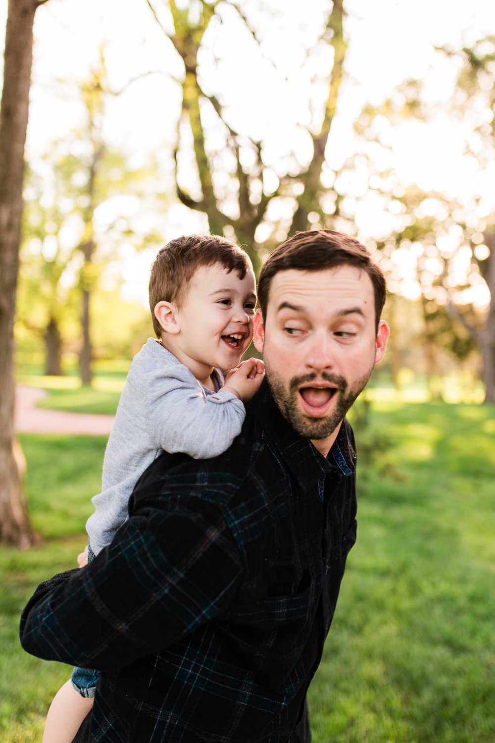 Father gives his son a piggyback ride in the park, Kansas City lifestyle photographer, Rebecca Clair Photography