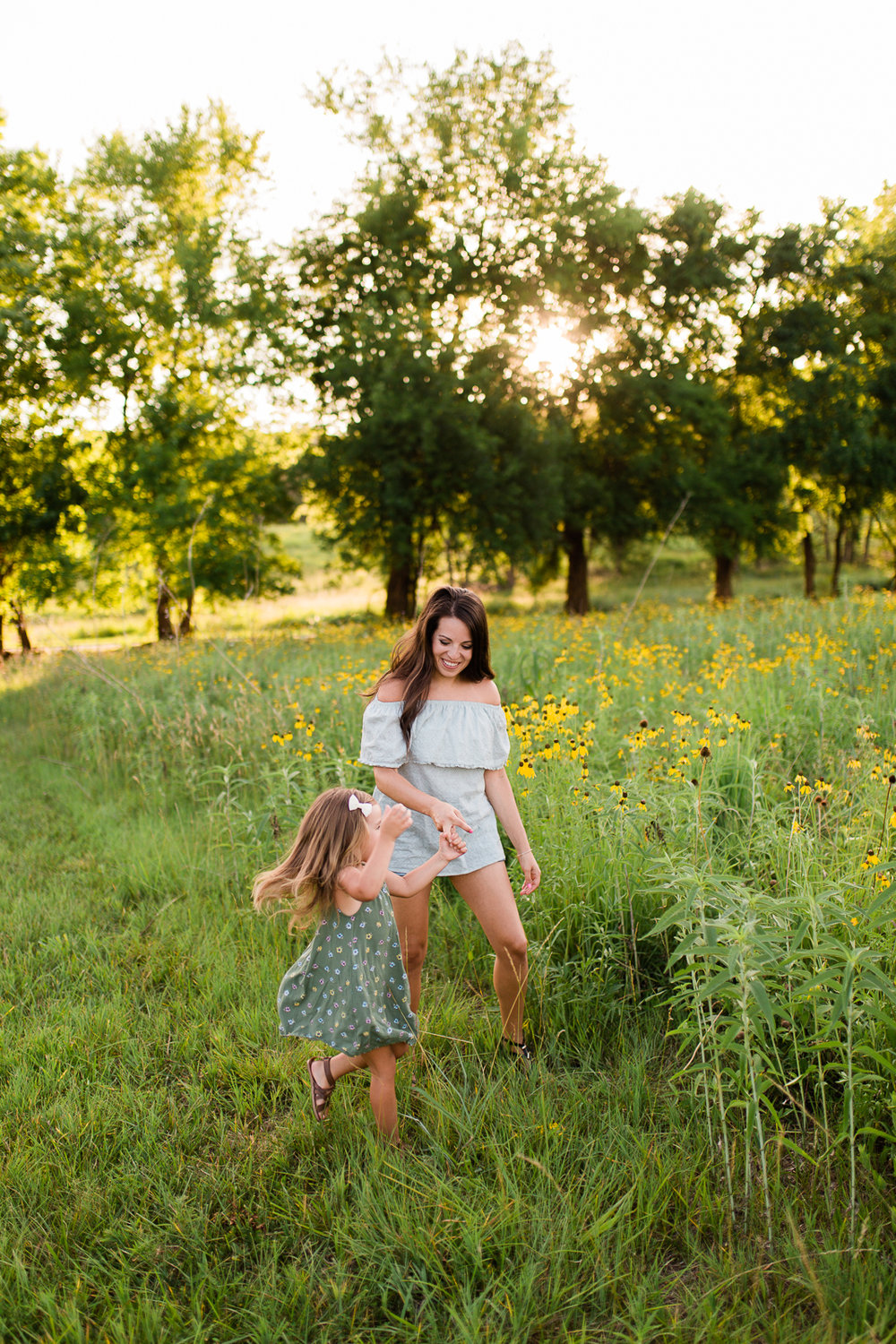 Mother dances with her daughter by a field of flowers, mommy and me session at Shawnee Mission Park, Kansas City family photographer