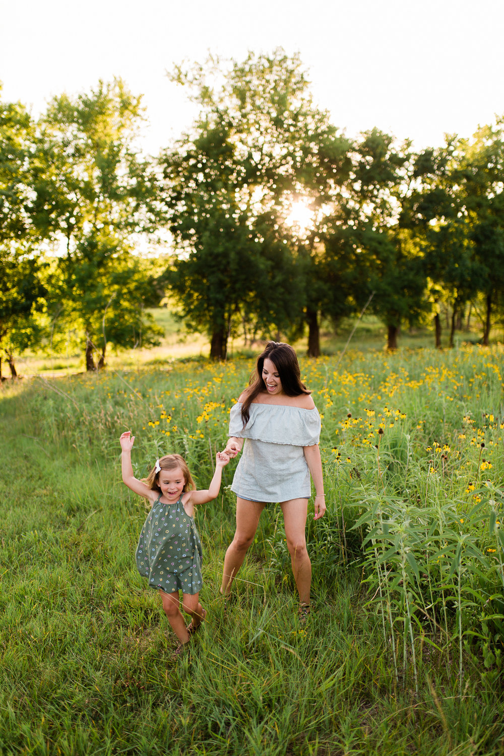 Mother twirls with her daughter, mommy and me session at Shawnee Mission Park, candid family photos in Kansas City