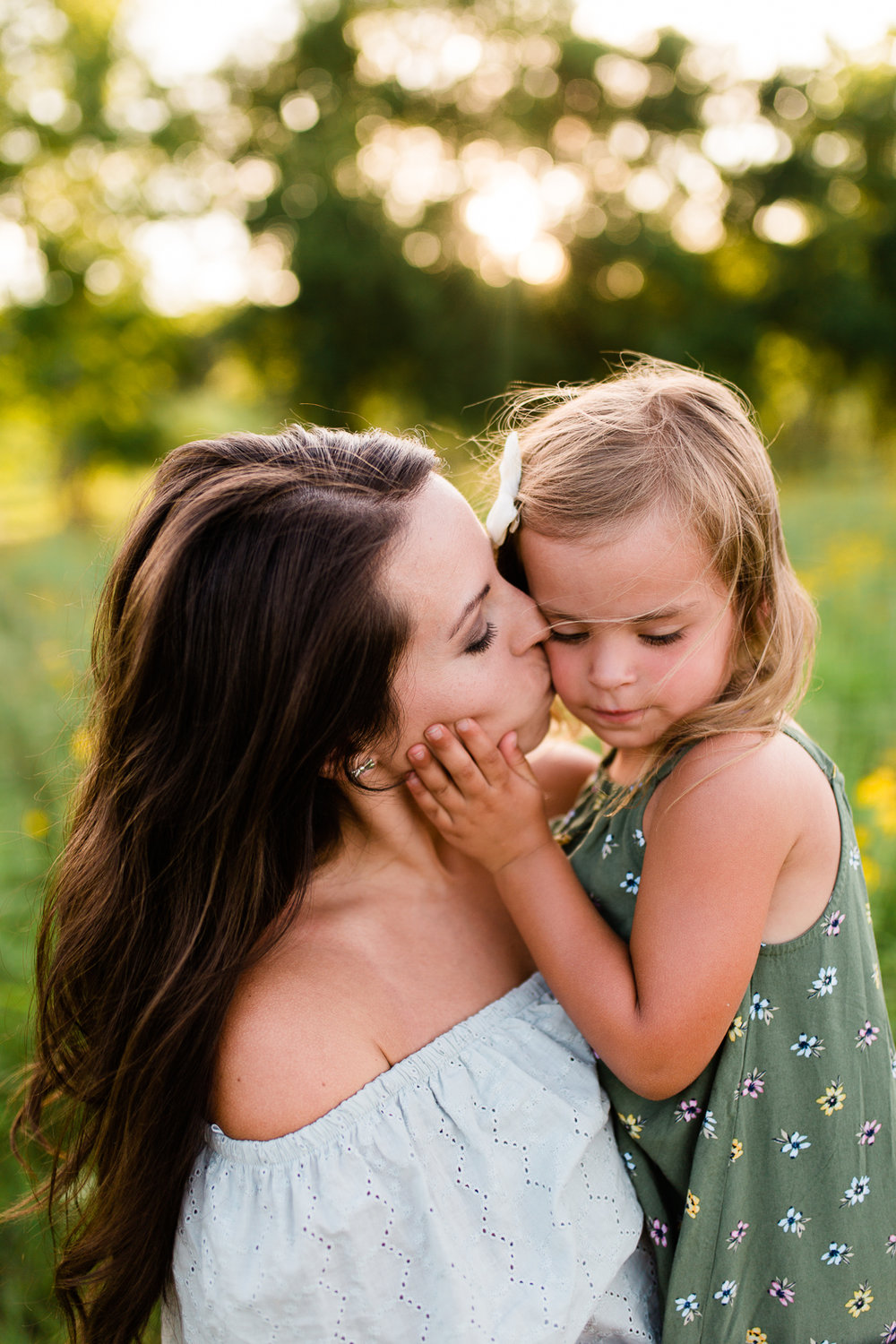 Mother kisses daughter's cheek, golden hour mommy and me session at Shawnee Mission Park, Kansas City family photographer