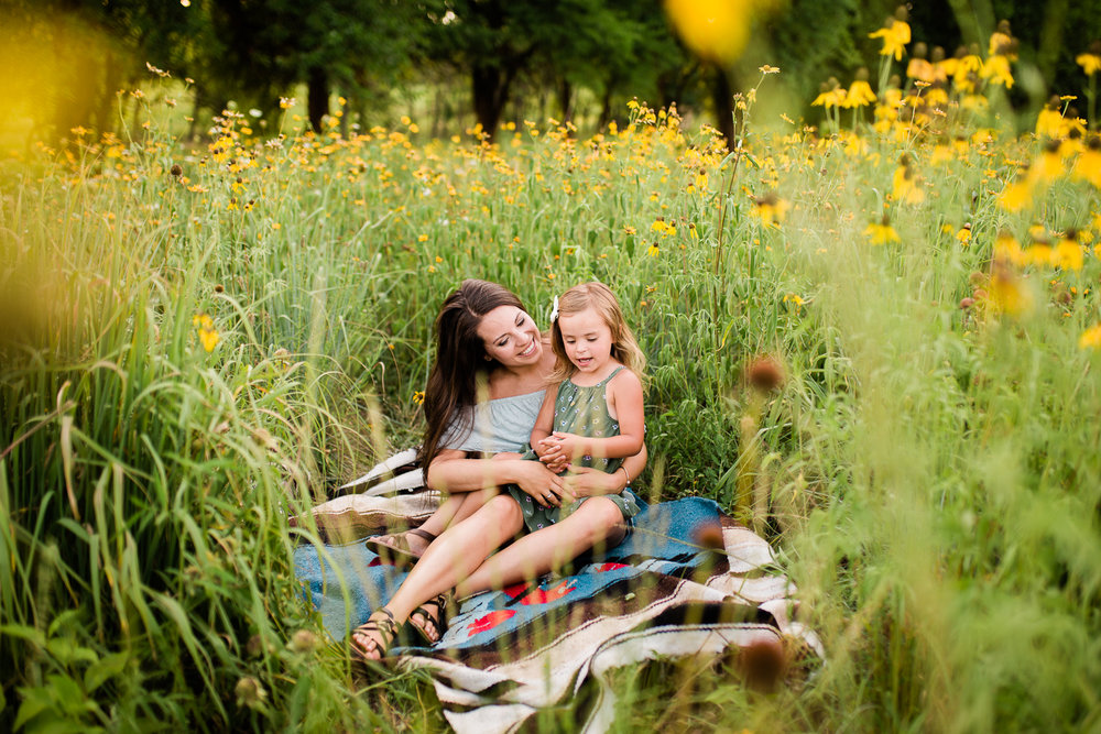 Mother and daughter cuddle on a blanket in a field of flowers, mommy and me session at Shawnee Mission Park, Kansas City family photographer