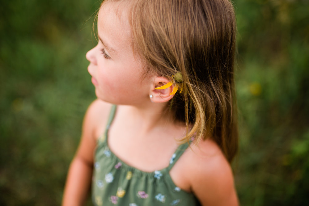 Close up portrait of a girl with a flower behind her ears, mommy and me session at Shawnee Mission Park, Kansas City candid children's portrait photographer