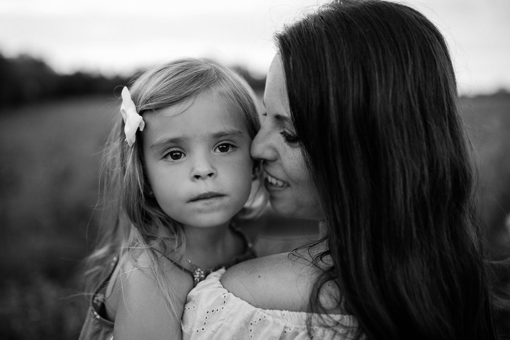 Black and white portrait of mother cuddling with daughter in a field, mommy and me session at Shawnee Mission Park, Kansas City emotive portrait photographer