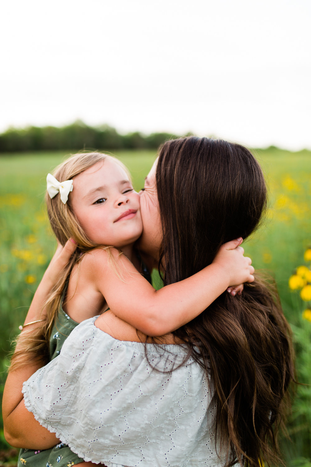 Daughter hugs mother in a field of flowers, mommy and me session at Shawnee Mission Park, Kansas City family photographer