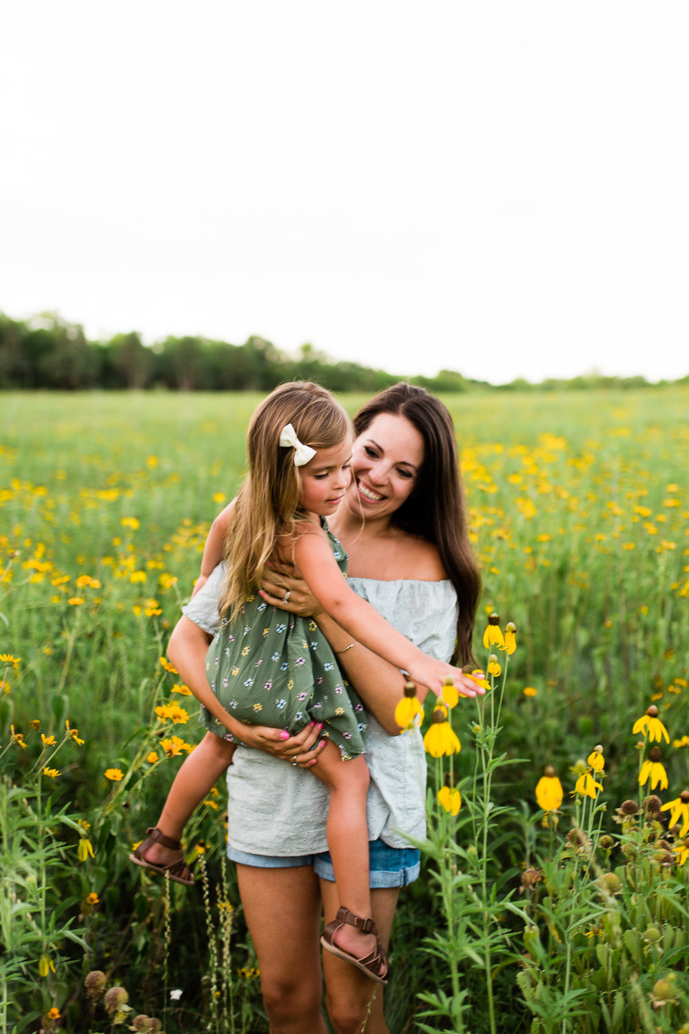 Mother carries daughter in a field of flowers, mommy and me session at Shawnee Mission Park, Kansas City family photographer