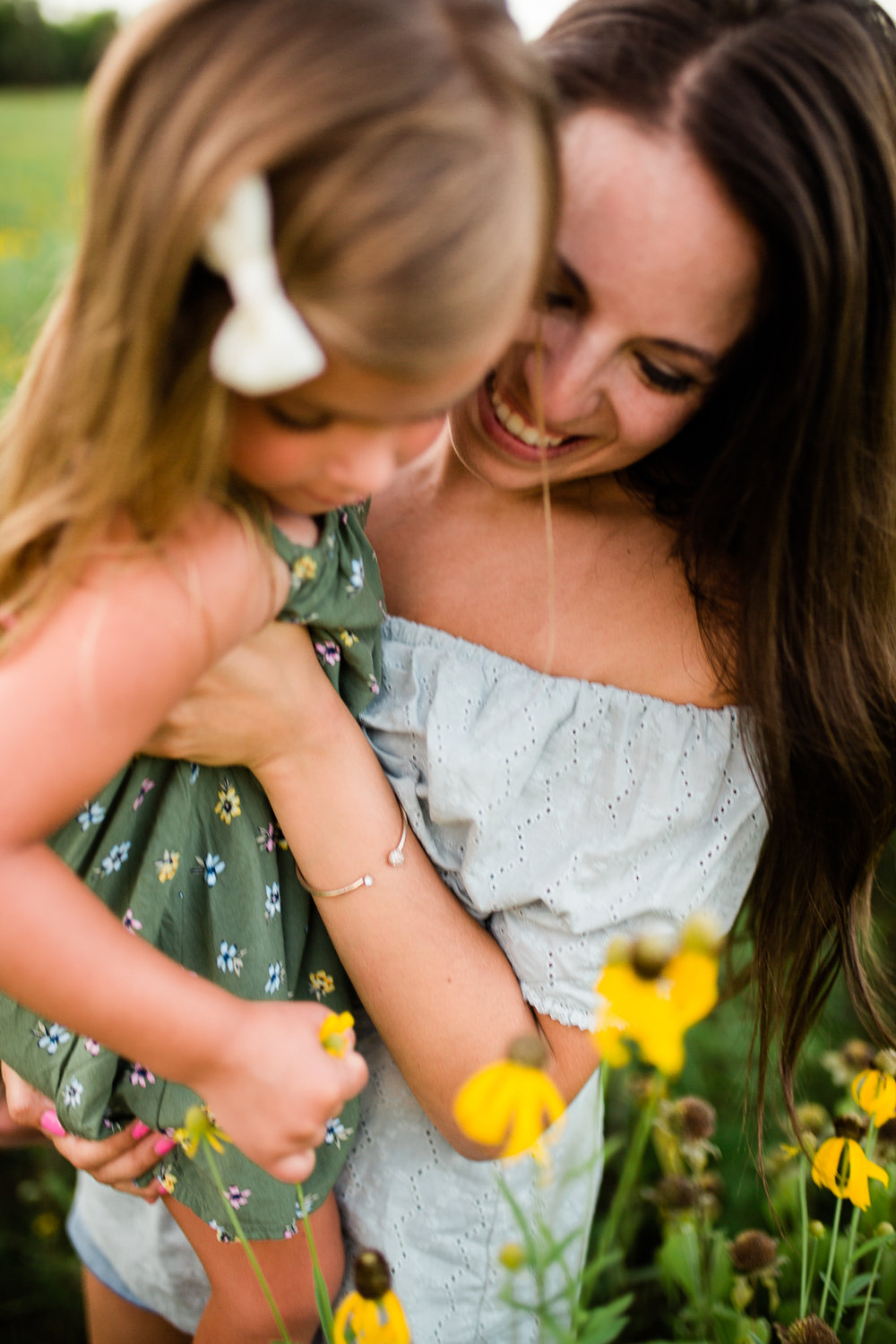 Close up photo of mother and daughter exploring flowers in a field, mommy and me session at Shawnee Mission Park, Kansas City candid family photos