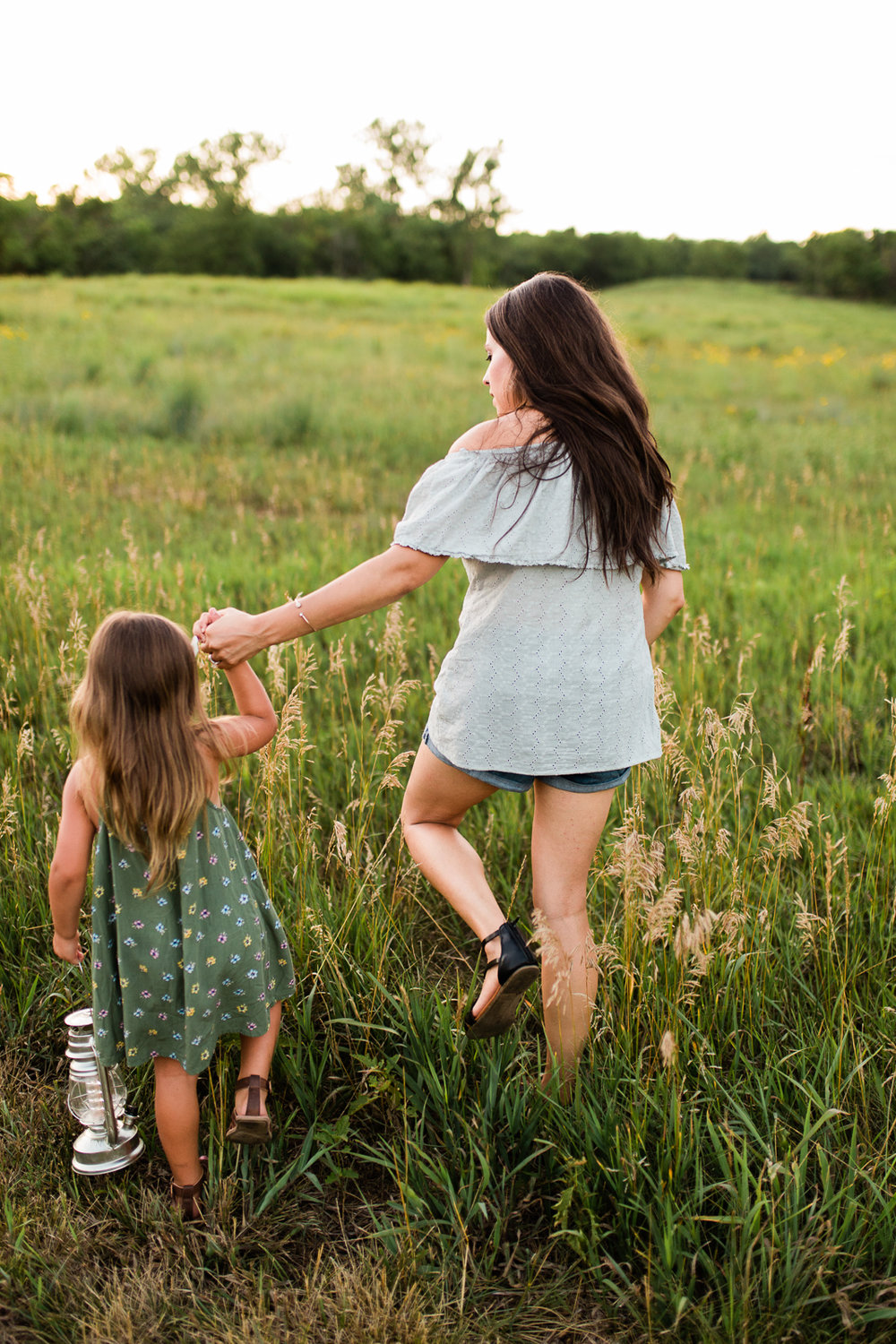 Mother and daughter walking into a field at sunset, mommy and me session at Shawnee Mission Park, Kansas City lifestyle photographer