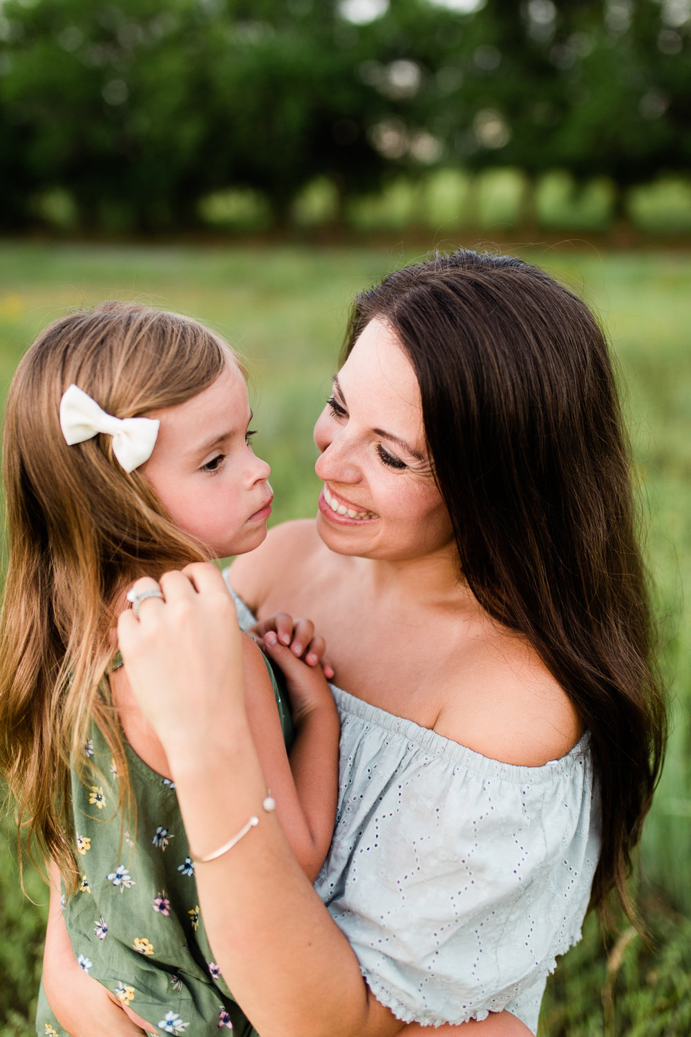 Mother caresses daughter's hair, mommy and me session at Shawnee Mission Park, Kansas City family photographer