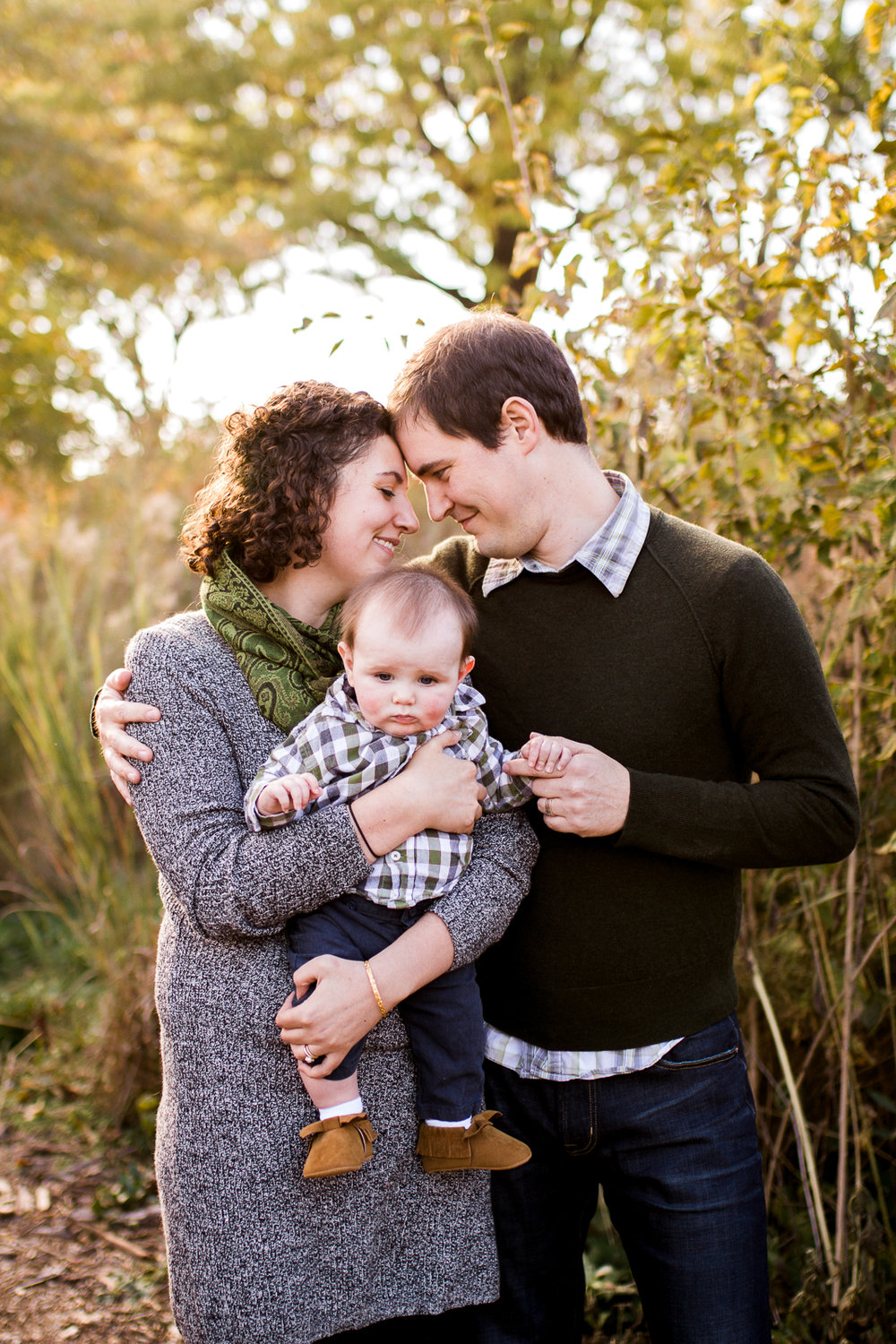 Parents touch foreheads as they hold their infant son, Kansas City lifestyle family photographer, fall family photos, Kansas City lifestyle mini sessions